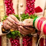 Engagement Ring ceremony- Indian Hindu male putting ring on bride's decorated finger. Couple is well attired as per traditional Indian Hindu wedding. Groom wearing Jodhpuri suit and floral garland.